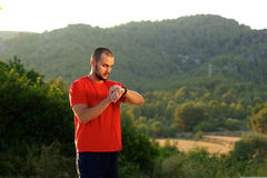 Healthy sports man standing outdoors looking at watch Stock Images