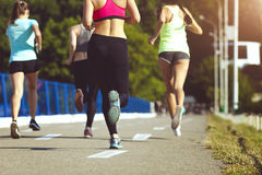 Healthy sports people trail running living an active life. Happy lifestyle athletes training cardio together in summer. Outdoors. Group women runs on the sports Stock Images