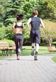 Healthy sports people trail running living an active life. Happy lifestyle couple of athletes training cardio together in summer o Stock Photography