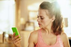 Sports woman watching fitness videos on internet via smartphone. Healthy sports woman in fitness clothes at modern home watching fitness videos on internet via royalty free stock photo