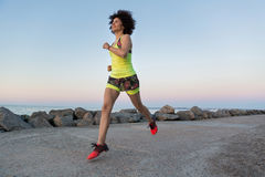 Healthy sportswoman running outdoors at the beach. Healthy young sportswoman running outdoors at the beach Royalty Free Stock Photography