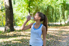 Healthy and Sporty Young Woman Drinking Water from Royalty Free Stock Photos