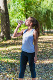 Healthy and Sporty Young Woman Drinking Water from Stock Photo