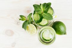 Healthy spring beverage in bottle and glass with cucumber, mint, lime, straw  on soft light wooden background. Copy space, top view, border Royalty Free Stock Photos