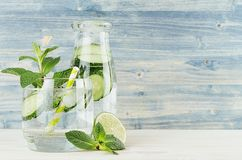 Healthy spring beverage in bottle and glass with green cucumber, mint, lime, straw on soft blue wooden background. Copy space royalty free stock images