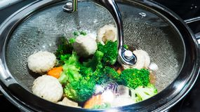 Healthy steamed vegetables in a pan full of boiling water and vapor stock image