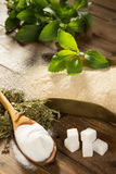 Healthy stevia or bad sugar. Unhealthy sugar on a wooden table together with natural sweetener stevia in powder, dried and fresh form Stock Image