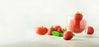 Healthy strawberry smoothie in glass on gray background with copy space. Banner. Summer food and clean eating concept. Vegan diet. Pink detox beverage with stock photo