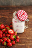 Healthy Strawberry smoothie or milkshake in jar and basket on old rustic background Stock Photo