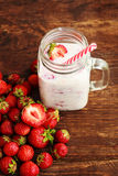 Healthy Strawberry smoothie or milkshake in jar and basket on old rustic background Stock Photography