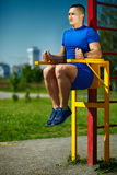 Healthy strong athlete man exercising at the city park Stock Photos