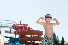 Healthy strong kid in sunglasses showing muscles in water park in summer day royalty free stock photo
