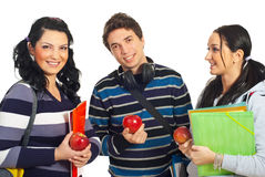 Healthy students holding apples. Healthy team of three students holding apples and notebooks isolated on white background Royalty Free Stock Photography