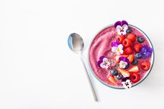 Healthy summer berry smoothie bowl with flowers and chia seed stock image