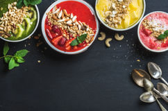 Healthy summer breakfast concept. Colorful fruit smoothie bowls with nuts and oat granola on black background Royalty Free Stock Photo