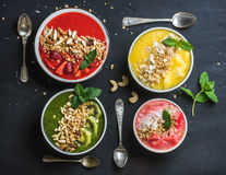 Healthy summer breakfast concept. Colorful fruit smoothie bowls with nuts, oat granola and mint leaves on black Royalty Free Stock Images