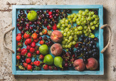 Healthy summer fruit variety. Black and green grapes, strawberries, figs, sweet cherries, peaches in blue wooden tray Royalty Free Stock Images