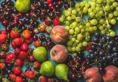 Healthy summer fruit variety. Black and green grapes, strawberries, figs, sweet cherries, peaches Stock Photos