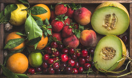 Healthy summer fruit variety. Melon, sweet cherries, peach, strawberry, orange and lemon on wooden tray background Royalty Free Stock Image
