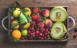 Healthy summer fruit variety. Melon, sweet cherries, peach, strawberry, orange and lemon in wooden tray over rustic Stock Photos