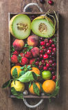 Healthy summer fruit variety. Melon, sweet cherries, peach, strawberry, orange and lemon in wooden tray over rustic Royalty Free Stock Photography