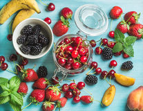 Healthy summer fruit variety. Sweet cherries, strawberries, blackberries, peaches, bananas and mint leaves on blue Stock Photography