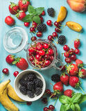 Healthy summer fruit variety. Sweet cherries, strawberries, blackberries, peaches, bananas and mint leaves on blue Stock Photo