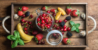 Healthy summer fruit variety. Sweet cherries, strawberries, blackberries, peaches, bananas and mint leaves Stock Photography