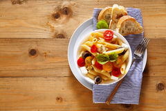 Healthy summer light pasta salad with fresh raw tomatoes, anchov. Ies and capers. on wood Royalty Free Stock Photography