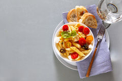 Healthy summer light pasta salad. With fresh raw tomatoes, anchovies and capers. glasses with water Stock Photography