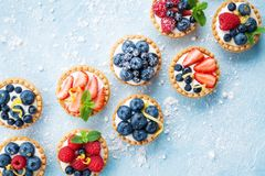 Healthy summer pastry dessert. Berry tartlets or cake with cream cheese top view. Stock Images
