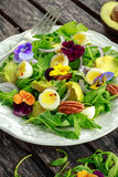 Healthy summer salad with quail eggs, avocado, pecans, wild rocket, red onion and edible viola flowers. Stock Images