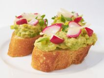 Healthy Summer Snack with avocado and radishes. Spread made of avocado and lemon juice on a traditional French baguette with radishes parsley leek and parmesan Stock Images