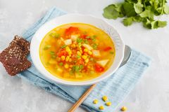 Healthy summer vegetable corn soup in a white plate with flax cr. Healthy bright vegetable corn soup in a white plate with crispy bread. Vegan Healthy Food royalty free stock images