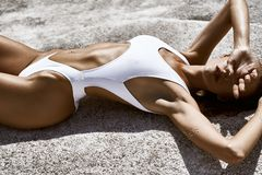 Healthy sunburnt girl in a bathing suit sunbathing in the sun. Healthy sunbathing girl in a bathing suit sunbathing and posing in the sun lying on a stone Royalty Free Stock Images