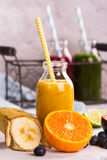 Healthy sweet yellow smoothie in a small glass bottle Royalty Free Stock Photo