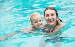 Healthy swimmers. Adorable mom and kid keeping fit and healthy in water Royalty Free Stock Photo