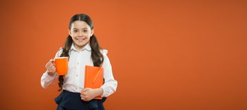 A healthy taste. Cute girl with tea cup and note book on orange background. Little schoolchild drinking tea for royalty free stock photos