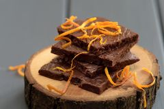 Healthy tasty dark chocolate bars with fresh orange rind on wood. Stands closeup stock photography