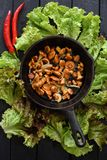 Healthy tasty forest mushrooms. Fried golden chanterelle mushrooms in cast iron pan served with lettuce and red chili peppers. Overhead view royalty free stock images