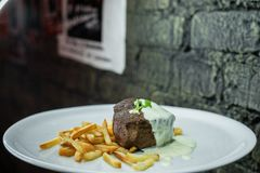 Healthy tasty grilled meat in sour cream sauce with french fries on a white plate in a restaurant. Dinner time. Healthy tasty grilled meat in sour cream sauce stock photo