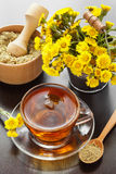 Healthy tea, bucket with coltsfoot flowers and mortar on table Stock Photo