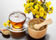 Healthy tea, bucket with coltsfoot flowers and mortar on table Royalty Free Stock Photos