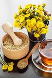 Healthy tea, bucket with coltsfoot flowers and wooden mortar on Royalty Free Stock Images