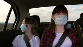 Healthy teenage girls in protective sterile medical mask ride in a taxi. The concept of a pandemic coronavirus. Free