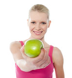 Healthy teenager offering green apple to you. Teenager offering green apple, full of vitamins isolated on white Stock Photos