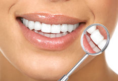 Healthy teeth. Healthy woman teeth and a dentist mouth mirror Stock Photo