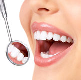 Healthy teeth. Healthy woman teeth and a dentist mouth mirror Royalty Free Stock Photos