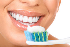 Healthy teeth. Smiling  young woman with healthy teeth holding a tooth-brush Stock Images