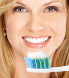 Healthy teeth. Smiling  young woman with healthy teeth holding a tooth-brush Stock Photography